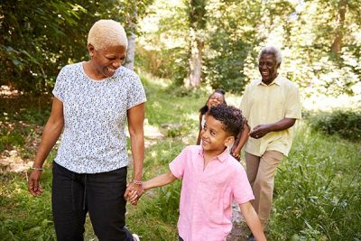 Photo: Black senior couple walking in forest with grandchildren
