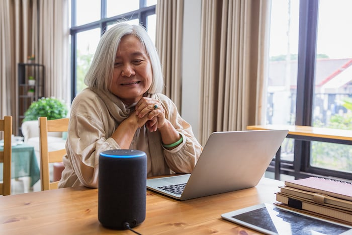 Asian senior woman seated at a dining table with an open laptop computer smiles as she uses smart speaker technology in the comfort of her independent residence at The Avenues Crofton Park